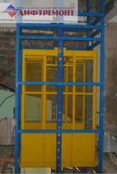Грузовой подъемник в металлокаркасной шахте.